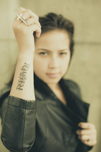 woman with a tattoo of the word forgiven
