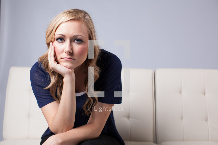 woman pouting a white couch