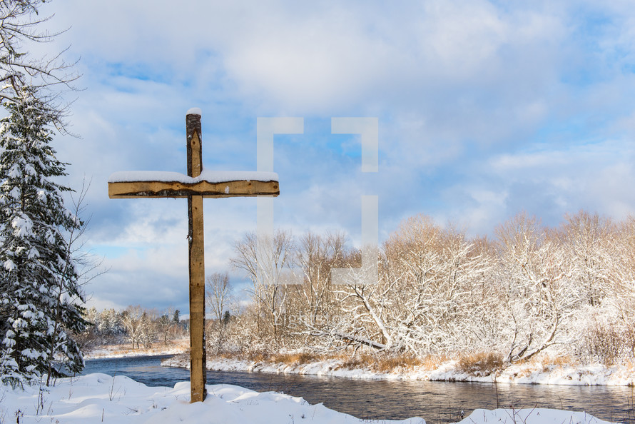 cross by a river in the snow