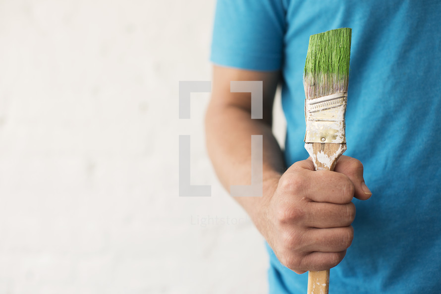 A man holds a paint brushes with green paint.