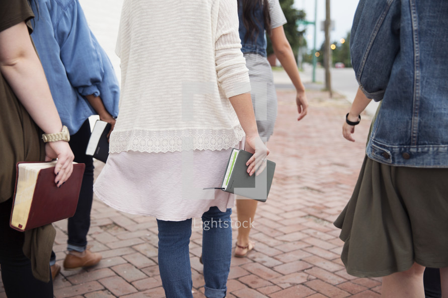 women walking carrying Bibles in the city.