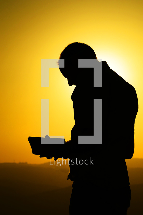 silhouette of a man reading a Bible