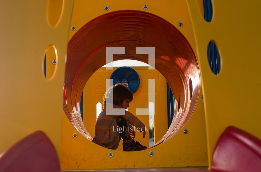 little girl sitting on  playground equipment