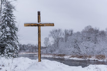 a cross by a river in the snow