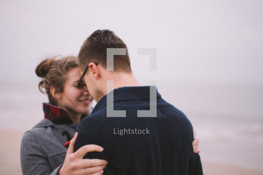 a man kissing a woman on a beach