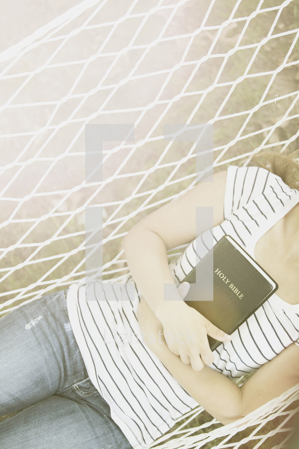 woman resting in a hammock holding a Bible