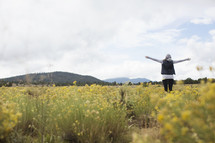 A woman stands with arms outstretched in a field.