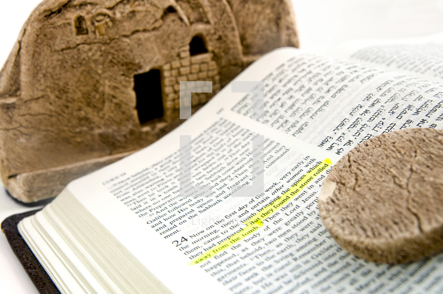 Bible open to The Gospel of Luke 24 in English and Hebrew with a Model of Jesus' Tomb and the stone which was rolled away.