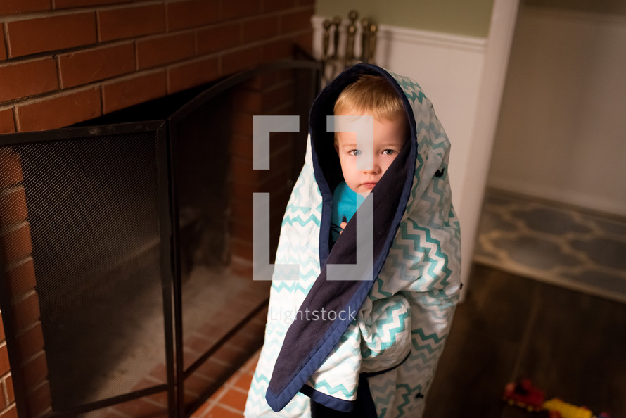 a toddler boy standing by a fireplace wrapped in a blanket