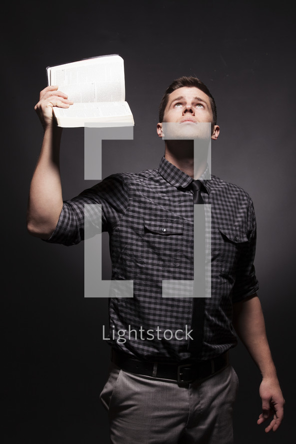 Man holding up Bible with one hand while looking to the heavens.