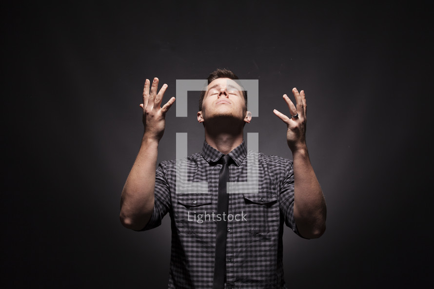 Man with hands riased looking to the heavens in prayer.