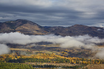 clouds hanging over a valley in fall