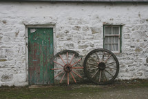 wagon wheels leaning against a house