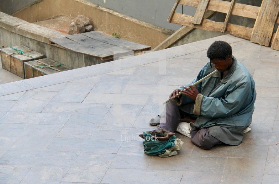 a man with a flute in a courtyard begging for money