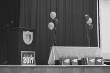 podium and balloons on stage for graduation 2017