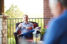 men sitting on a porch eating a snack and talking