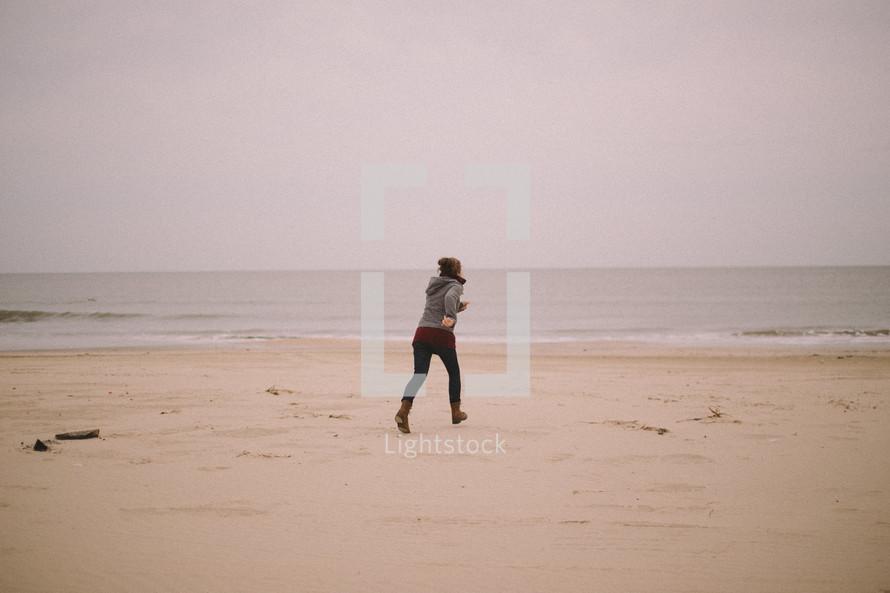 A woman on a beach jogs toward the ocean.