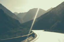 Sunshine on a highway winding through mountains.