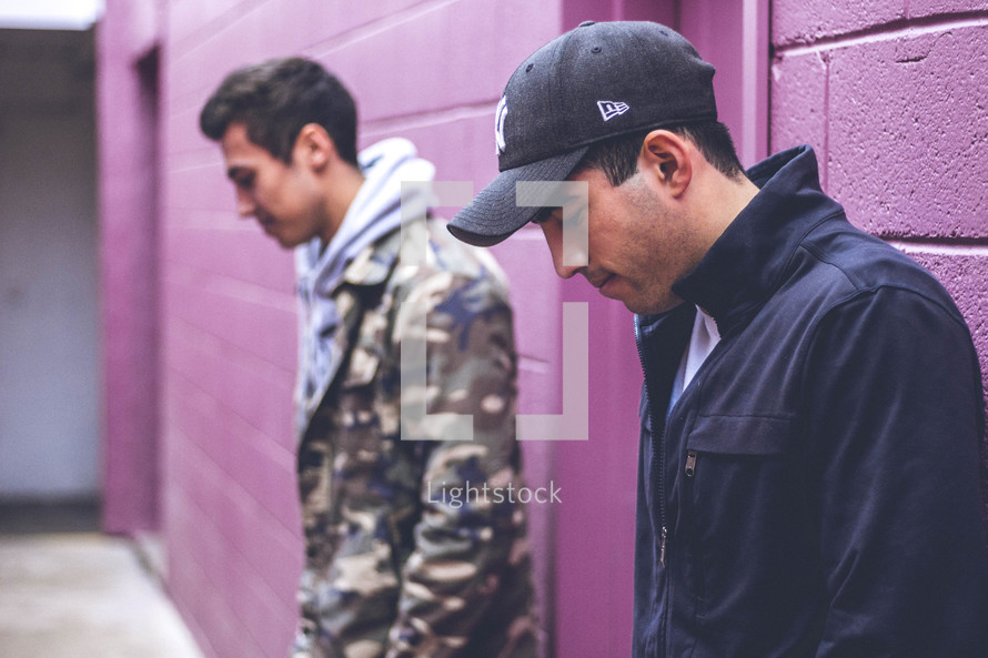 two men standing in an alley looking down