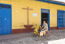 man riding a bicycle past a church