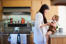 a mother talking to her toddler daughter who is sitting on a countertop