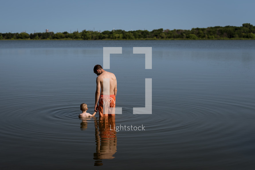 a father and son standing in a lake