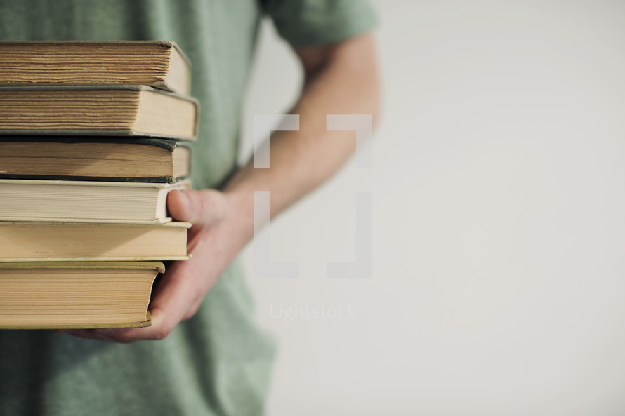 man holding a stack of books
