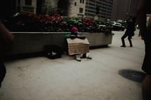 a man begging on a downtown sidewalk