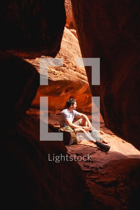 a man sitting on red rocks
