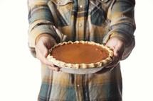 man holding a pumpkin pie