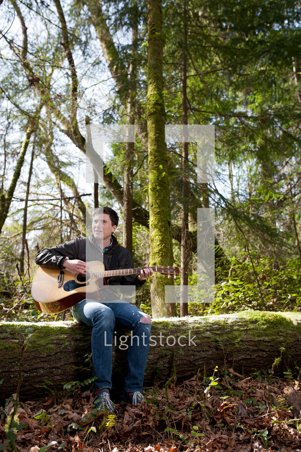 man playing a guitar and singing in a forest