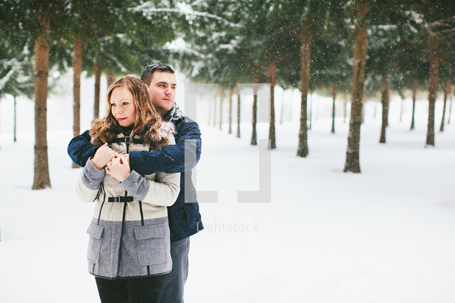 a couple standing in falling snow
