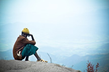 man sitting on a mountaintop