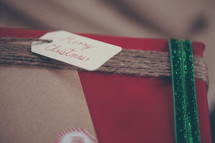 """A gift wrapped in Christmas paper with a tag saying, """"Merry Christmas."""""""