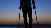 silhouette of a crippled man in arm braces