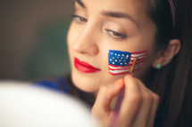 woman with face paint of a flag for July 4th