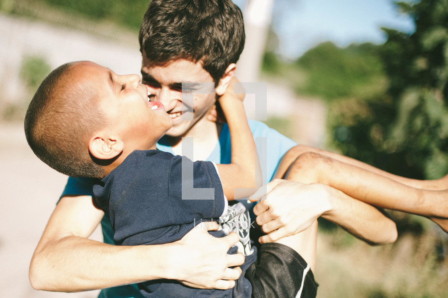 A teen carrying a younger boy.