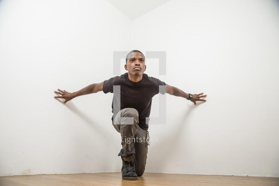 man pushing against a wall