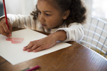 a girl child coloring a heart on paper