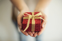 a woman holding a wrapped gift.