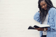 A young woman standing and reading the Bible