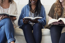 young women sitting on a couch talking, laughing, and reading bibles