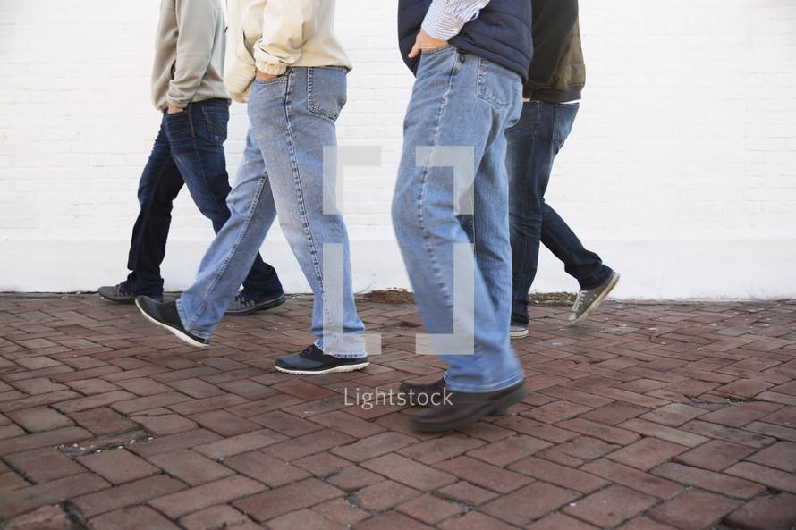 Group of men walking down a sidewalk.