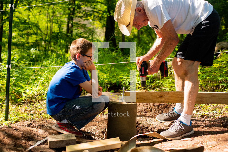 a grandson and grandfather drilling a hole into a board