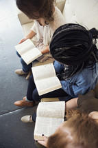 young women sitting on a couch reading bibles
