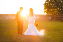 a bride and groom standing under intense sunlight in grass outdoors