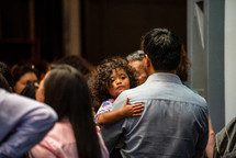 a father holding his toddler daughter during a worship service