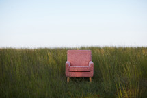 empty chair in a field of tall grasses