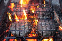 Hamburgers on the grill over a camp fire