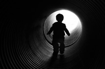 child walking through a pipe tunnel
